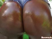 Ebony babe shakes her oily butt outdoors